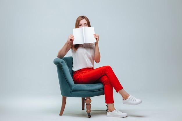 Mädchen in roten hosen sitzt auf einem stuhl und liest ein buch mit weißem einband