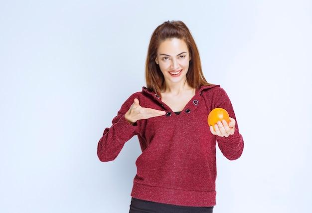 Mädchen in roter jacke mit einer orange