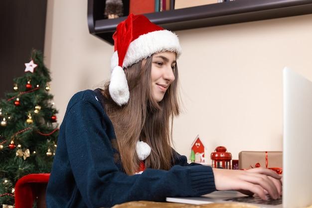Mädchen in santa claus hut spricht mit laptop für videoanruf freunde und eltern. das zimmer ist festlich eingerichtet. text-chat