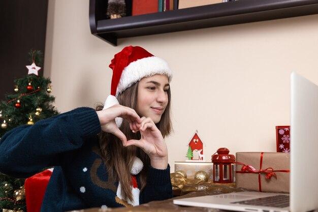 Mädchen in santa claus hut spricht mit laptop für videoanruf freunde und eltern. das zimmer ist festlich eingerichtet. weihnachten während des coronavirus. herzform