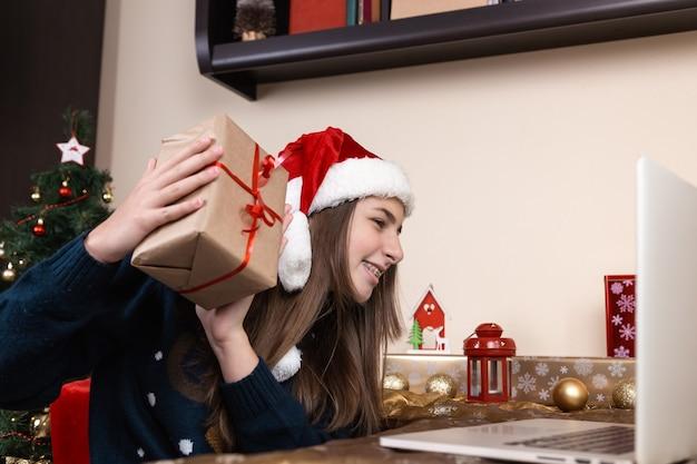 Mädchen in santa claus hut spricht und gibt ein geschenk mit laptop für videoanruf freunde und eltern. das zimmer ist festlich eingerichtet. weihnachten während des coronavirus.