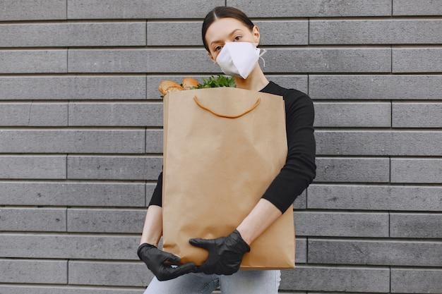 Mädchen in schutzmaske hält paket mit produkten