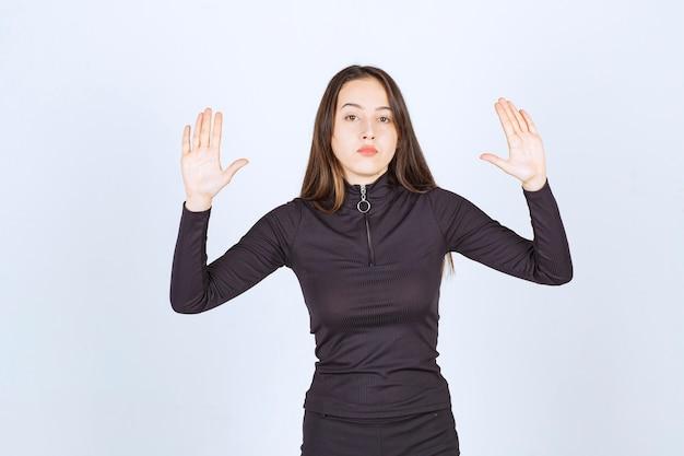 Mädchen in schwarzen kleidern, die versuchen, etwas aufzuhalten.