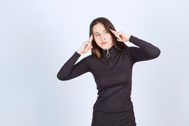 Mädchen in schwarzen kleidern sieht nachdenklich und zweifelhaft aus.