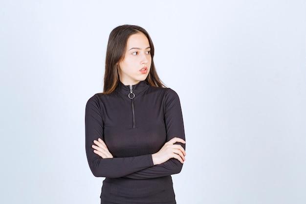 Mädchen in schwarzer kleidung, die professionelle und neutrale posen ohne reaktion gibt.