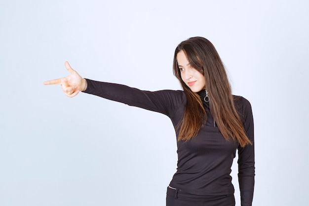 Mädchen in schwarzer kleidung zeigt auf etwas auf der linken seite.