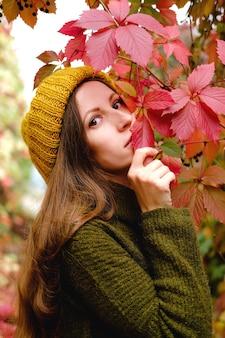 Mädchen in senfgelber strickmütze und sumpfgrüner wollpullover, der unter buntem efeu im herbst geht.