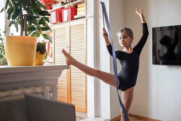 Mädchen in sportbekleidung, das sportwettkampf online beobachtet und übungen in der rhythmischen gymnastik wiederholt