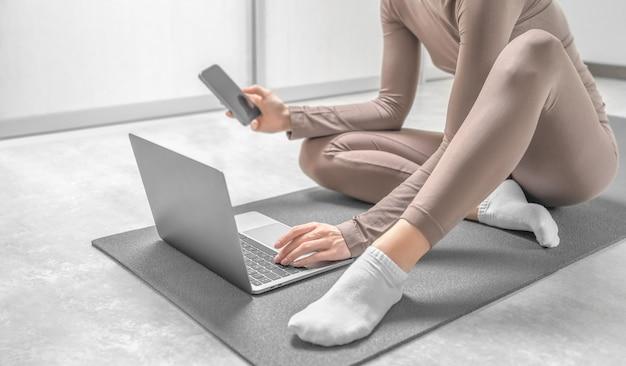 Mädchen in sportkleidung, die auf der trainingsmatte sitzt und auf dem laptop und telefon nach online-training sucht.