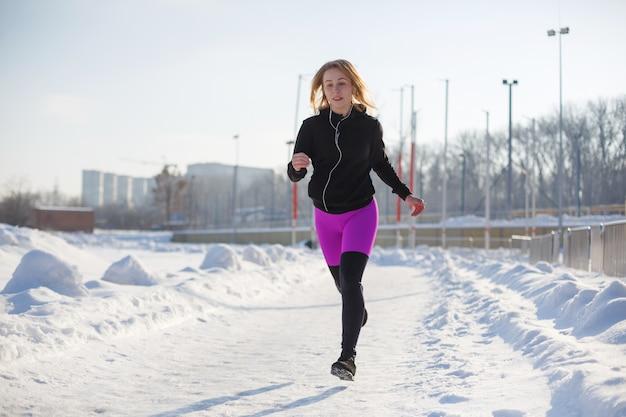 Mädchen in sportkleidung laufen auf einem schneebedeckten stadion fit und sport lifestyle. laufen und musik hören. sport lebensstil
