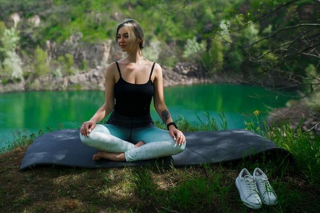 Mädchen in sportkleidung meditiert am see