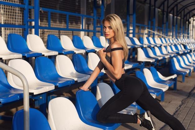 Mädchen in sportkleidung mit perfektem körper posiert im stadion