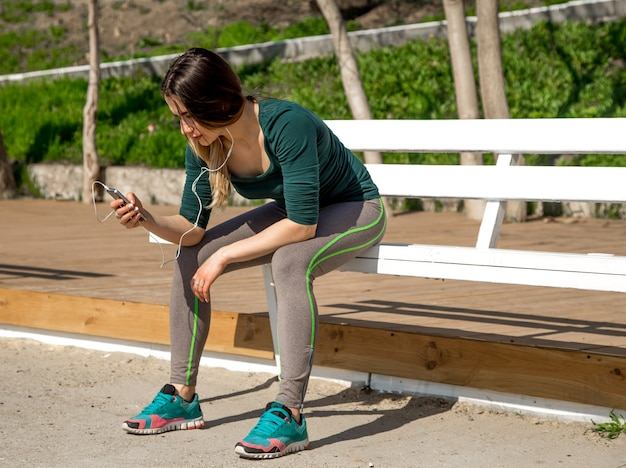 Mädchen in sportkleidung sitzt auf der bank und hört musik, fitness, sportmotivation, sport, fitness