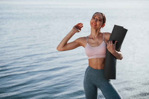 Mädchen in sportlicher kleidung steht gegen wasser an der wand