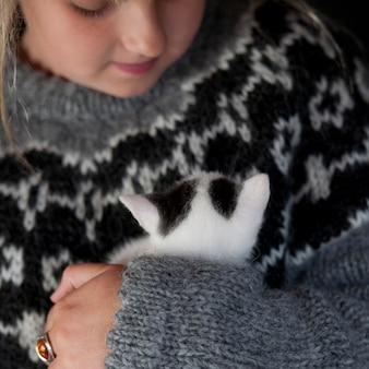 Mädchen in strickpullover mit kätzchen