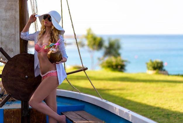 Mädchen in trinkendem kokosnusssaft des weißen hutes in einem boot in dem meer