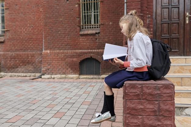 Mädchen in uniform mit rucksack, der im schulhof sitzt und notizbuch liest, kopienraum. zurück zur schule, unterrichtsbeginn, bildung, wissen, unterricht, kinderkonzept