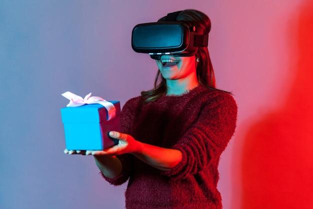 Mädchen in vr, das eine verpackte geschenkbox hält und freudig lächelt und einem virtuellen freund ein weihnachtsgeschenk gibt