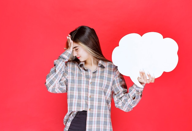 Mädchen in warmem pullover, das ein ideenboard in wolkenform hält und sich aufgrund dieser aktivität müde fühlt