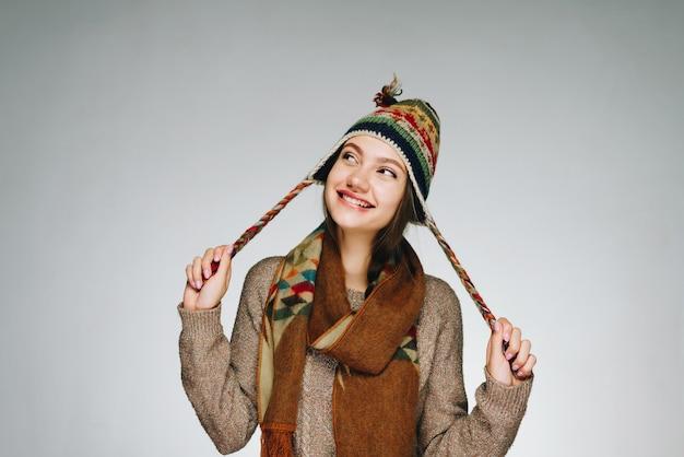 Mädchen in warmen kleidern mit einem schlauen blick und einem breiten lächeln schaut auf