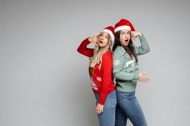 Mädchen in weihnachtsmützen rufen über handgesten an.