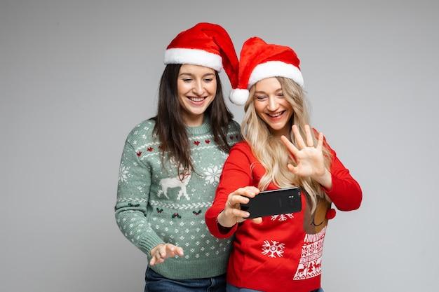 Mädchen in weihnachtsmützen videoanrufe über handy.