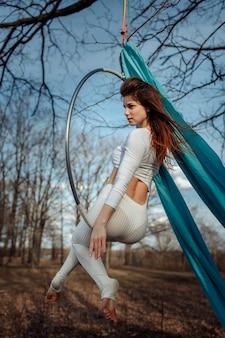 Mädchen in weiß auf einem reifen im wald