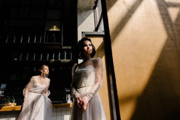 Mädchen in weißen brautkleidern posieren
