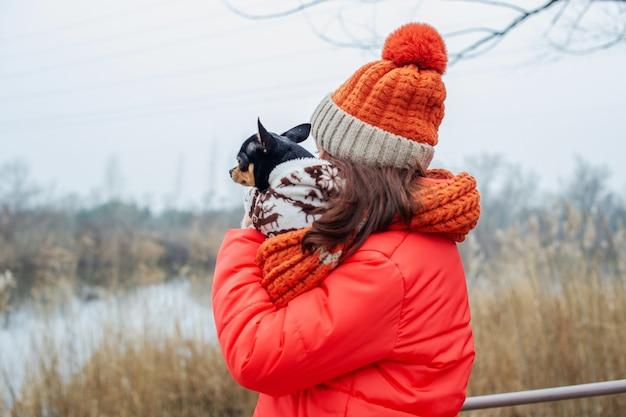 Mädchen in winterkleidung. teenager-mädchen in einer orange jacke, orange hut und schal. mädchen und chihuahua