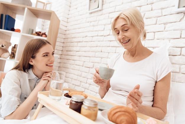 Mädchen interessiert sich für ältere frau im bett zu hause.