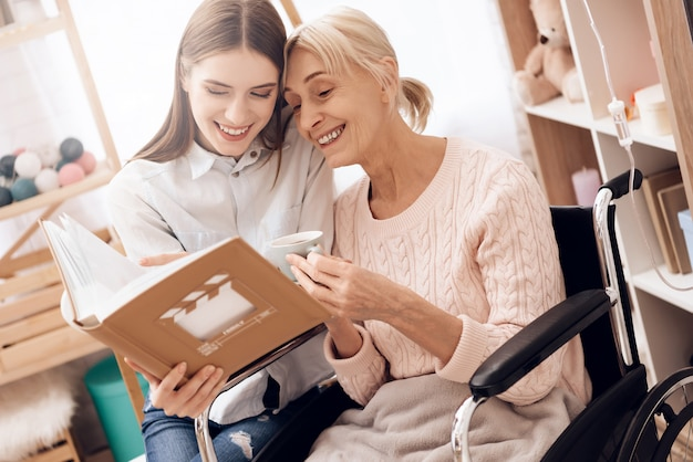 Mädchen interessiert sich für ältere frau im rollstuhl zu hause.