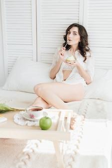Mädchen isst kuchen zum frühstück im bett
