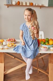 Mädchen isst süße macaron in der küche