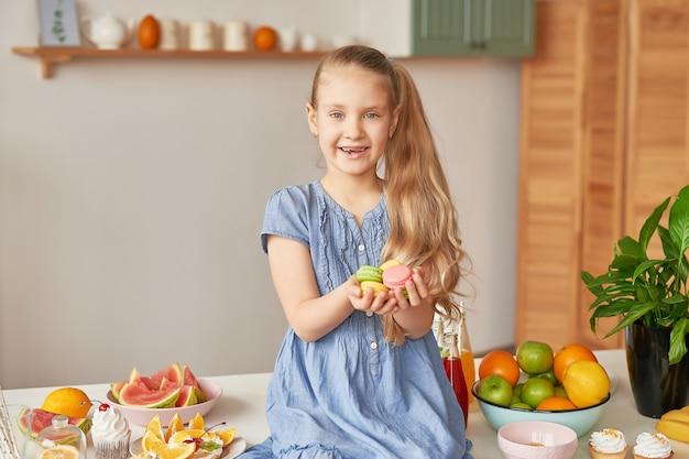 Mädchen isst süße macarons in der küche