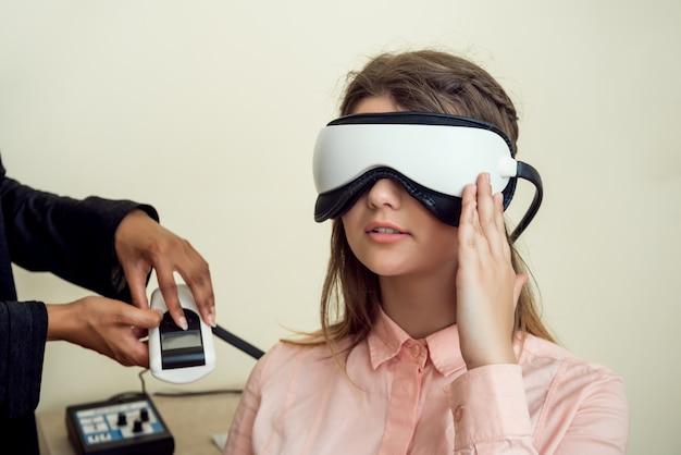 Mädchen ist besorgt um ihre sicht. entspannte moderne europäische frau, die im büro des augenpflegespezialisten sitzt und wartet, wenn der eingriff abgeschlossen ist, und während der untersuchung einen digitalen sichtprüfer trägt