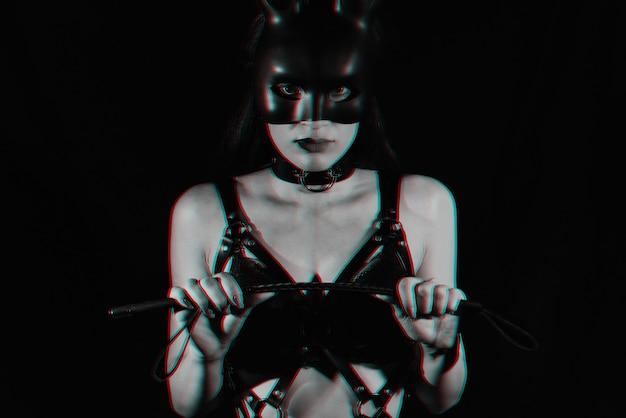Mädchen ist eine sexy geliebte in einem ledergürtel mit einer bdsm-peitsche in der hand und einer hasenmaske