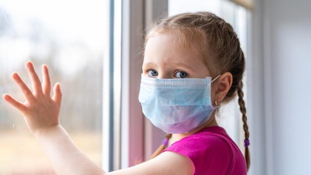 Mädchen ist krank und kann nicht nach draußen gehen, schaut aus dem fenster und sitzt zu hause. coronavirus