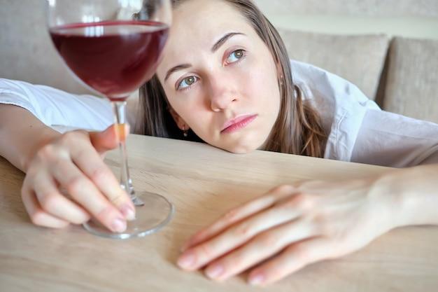Mädchen ist traurig mit einem glas wein am tisch.