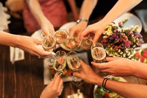 Mädchen jubelt gläsern mit champagner im restaurant zu