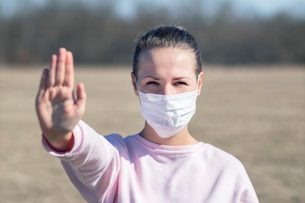 Mädchen, junge frau in der sterilen medizinischen schutzmaske auf ihrem gesicht, das kamera draußen betrachtet, handfläche, hand zeigen, kein zeichen stoppen. luftverschmutzung, virus, chinesisches pandemie-coronavirus-konzept. covid-19