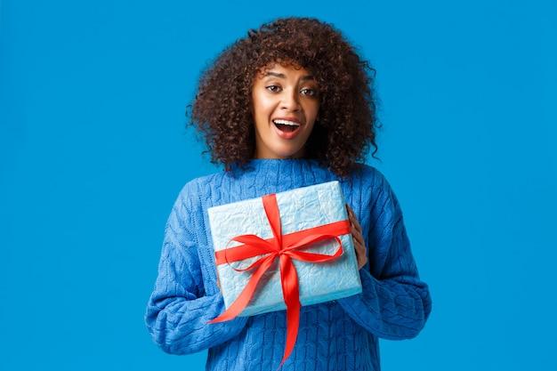 Mädchen kann es kaum erwarten, geschenke in der winterferienzeit auszupacken. weibliche holding des netten und reizenden freundinafroamerikaners wickelte geschenk ein und lächelte und dankte der stellung des blaus
