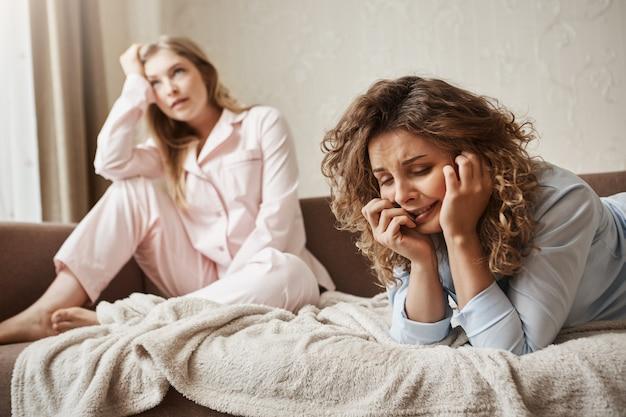 Mädchen kann nicht mit druck umgehen, fühlt sich elend und traurig. düstere weinende frau, die in nachtwäsche auf sofa liegt, jammert und sich über das leben beschwert, während freundin sich mit dummen gesprächen belästigt fühlt
