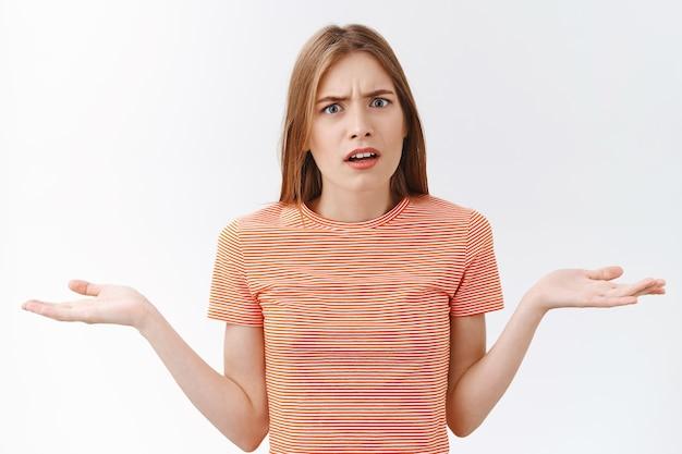 Mädchen kann nicht verstehen, was dein problem ist. angepisste, verzweifelte junge freundin im gestreiften t-shirt, die vor bestürzung und enttäuschung die hände zur seite hebt, verwirrt anstarren, verwirrt, was passiert ist