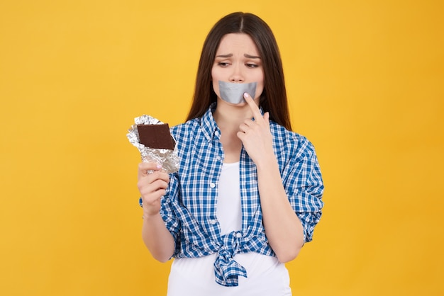 Mädchen kann schokolade auf gelbem hintergrund nicht essen.