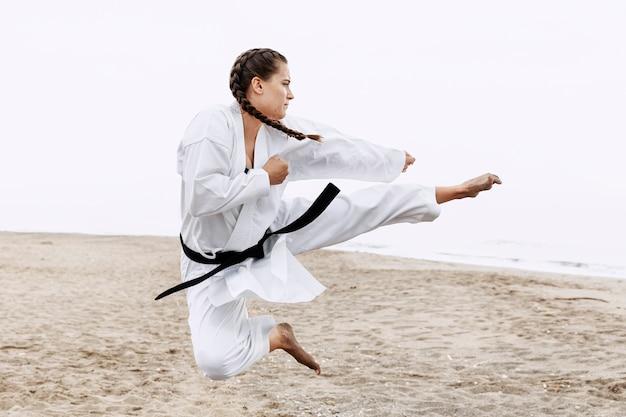 Mädchen-karatetraining mit vollem schuss