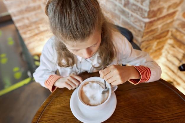 Mädchen kind 9, 10 jahre alt mit tasse heißer schokolade im café am tisch sitzen.
