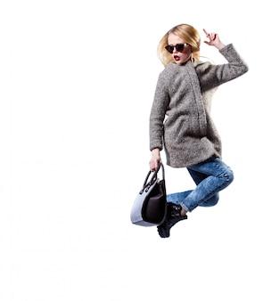 Mädchen kleidete im grauen pelzmantel an und trug die sonnenbrille und schwarze tasche und warf auf weißem hintergrund auf. sexy schönheit mode blond.