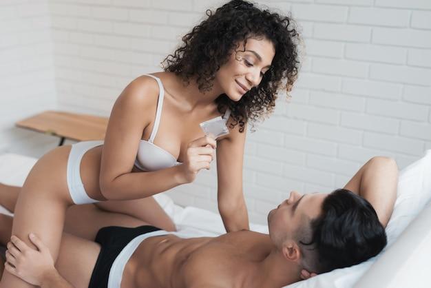 Mädchen kletterte auf den mann und hält ein kondom in den händen.