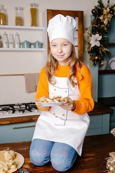 Mädchen kochte kekse, um weihnachten in der küche zu hause zu feiern