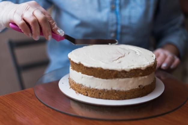 Mädchen konditor macht eine hochzeitstorte mit seinen eigenen händen und drückt die sahne auf den kuchenschichten